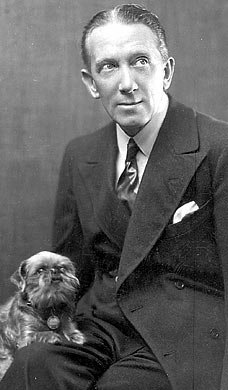 Gerald du Maurier, seated with a dog