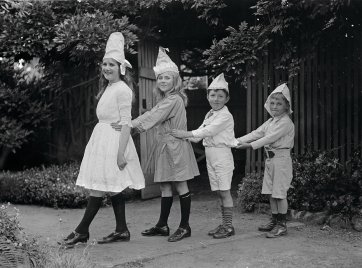 Two girls and two boys wearing party hats, standing in line by Ruth Hollick