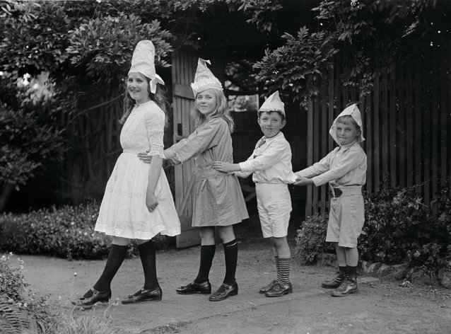 Two girls and two boys wearing party hats, standing in line