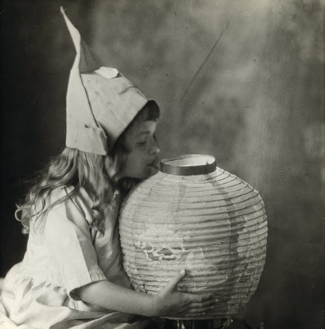 Young girl holding a Chinese paper lantern, wearing a hat