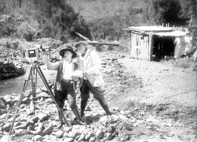 Louise Lovely and Wilton Welch setting up a camera on a rocky river bank by John H Robinson