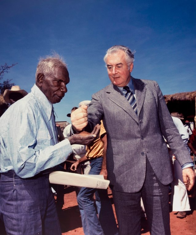 Prime Minister Gough Whitlam pours soil into the hand of traditional land owner Vincent Lingiari