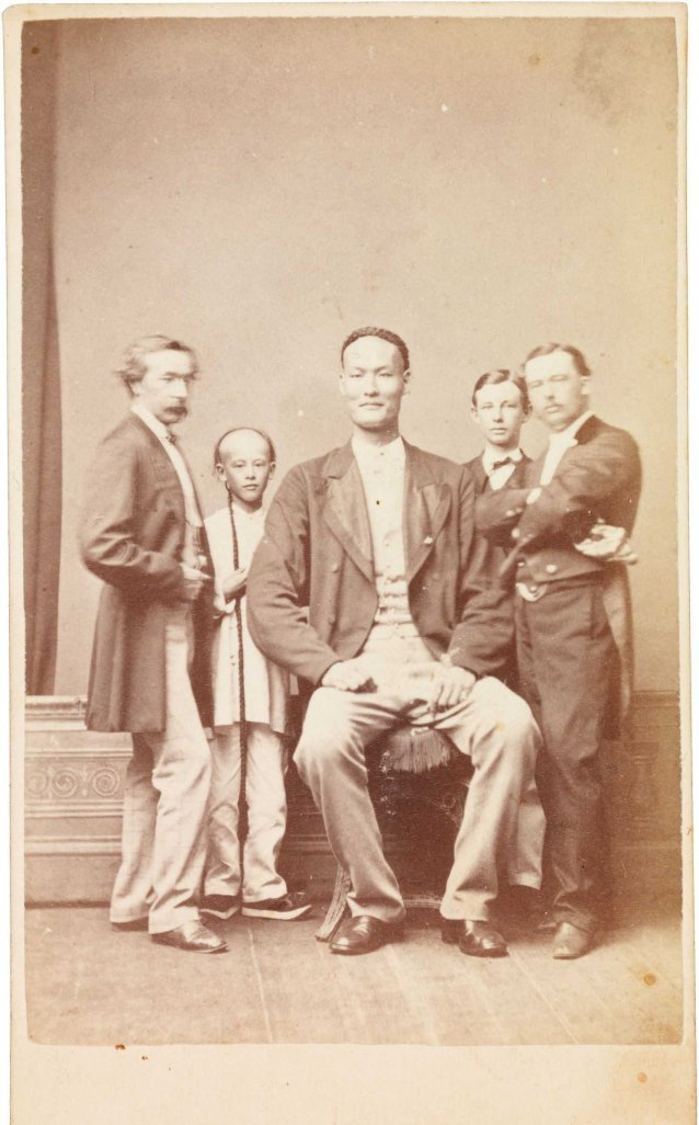 Chang the Chinese giant in European dress with Chinese boy and three European men, one of whom is his manager