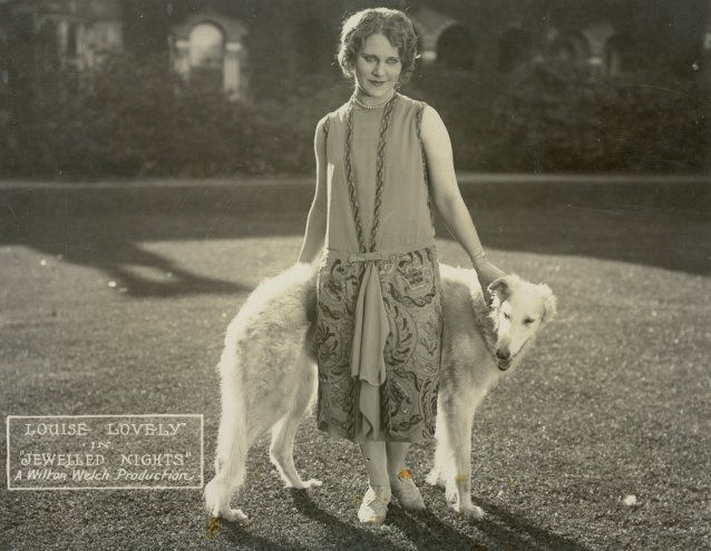 Jewelled Nights: Louise Lovely poses with a large dog by Walter Sully