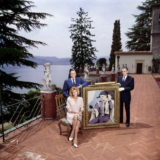 "Baron and Baroness Thyssen-Bornemisza pose on the terrace of Villa Favorita with Picasso's 1923 ""Harlequin with a Mirror"""