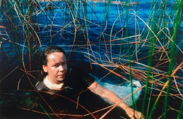 After Ophelia: Fiona Foley at Lake Mackenzie, Fraser Island (Referencing Ophelia by John Everett Millais), 1994 by Juno Gemes